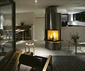 A fire burning in a stainless steel fireplace in an open plan living room-cum-dining room