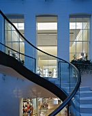 Curved exterior staircase in the twilight and a view into an illuminated loft like apartment