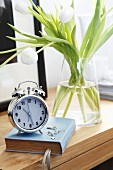 An alarm clock, a book and white tulips of a bedside table