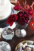 Red roses, stones and snow globe being used as table decorations