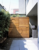A wooden partition wall with a modern relief pattern on the terrace of a house