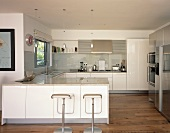 Open white designer kitchen with chrome swivel bar stools in front of a counter