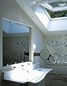 Curved designer sink with a recessed mirror in the wall and open skylight window