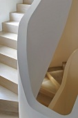 Winding staircase with wooden treads and stone railing