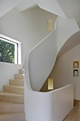 A curved staircase with wooden steps and a concrete designer bannister