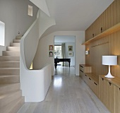 Modern staircase with wood paneled walls and custom made built-in and a view through an open passage at a grand piano