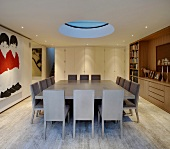 Large dining table with gray chairs under a circular skylight in a modern dining room