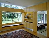 Raumecke mit massgefertigtem Einbau aus Holz übereck vor Fensterfront und Orientteppich