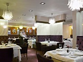 Tables set in a hotel restaurant and seats upholstered in dark leather in front of a room divider covered in fabric