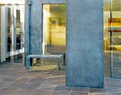 Tiled lobby and steel room divider in front of a bench by a bank of windows