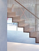 Contemporary staircase with metal grid dividing the staircase from the rest of the room