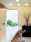 Küchenblock mit weisser Arbeitsplatte vor Fenster mit Landschaftsblick in Designerküche
