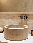 Circular sink made of beige stone and wall fitting on a wall covered in sand colored tiles