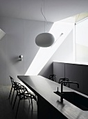 White hanging lamp above a breakfast bar with integrated sink and designer chairs