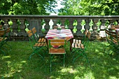 A garden table and chairs in front of a stone balustrade
