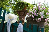 A summer hat and a sculpture on a garden fence