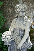A stone statue with a flower basket