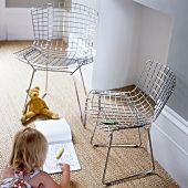 A pair wire mesh chairs and little girl drawing on the carpet