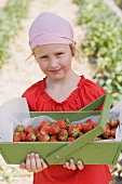 A girl holding a wooden basket of strawberries