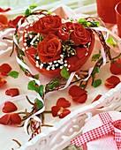 Rote Rosen und Schleierkraut in roter Herzschale