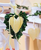 Heart-shaped box wreath around metal heart on chair back