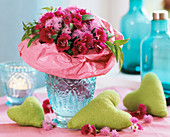 Bouquet of pinks with pink paper frill in blue glass vase