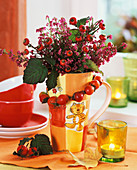 Arrangement of heather and rose hips in coffee mug