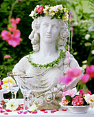 Bust of woman with flower wreath on table in open air