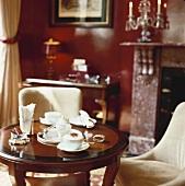 Cappuccino auf rundem Tischchen mit Posterstühlen vor Kamin