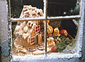 Gingerbread house through a snowy window