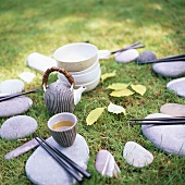 Still life with tea, chopsticks and stones in the open air
