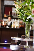 Vase of flowers on a table in a champagne bar