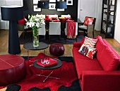 Living room with red couch, dining area in background