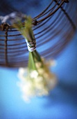 Lilies of the valley tied to wire basket