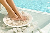 Feet on plate of stones in water