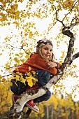 Girl sitting in an autumn tree