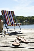 Deck chair and flip flops on a wooden jetty on the lake