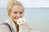 Teenage holding a bunch of daisies at the beach