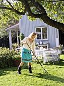 Woman raking up grass clippings in garden