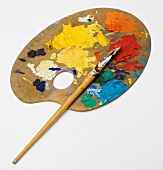 Artist's palette with paint in front of a white background