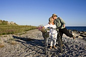 Older couple with bicycles kissing on beach