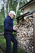 Älterer Mann mit Holzscheiten am Kaminholzunterstand