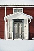weiße überdachte Eingangstür eines braunen Holzhauses im Winter