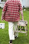 Man carrying paint pot & bench