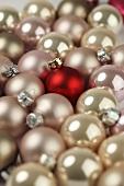 Viele rosa Weihnachtskugeln und eine rote Kugel