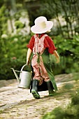 A little girl dressed as a gardener with a watering can