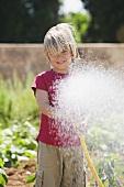 A boy spraying water from a garden hose