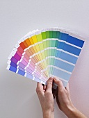 A woman holding colour charts