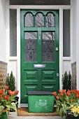 Hauseingang mit Frühlingsblumen in Töpfen & Recycling-Box vor grüner Haustür