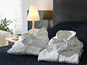 Folded bathrobes on a hotel bed